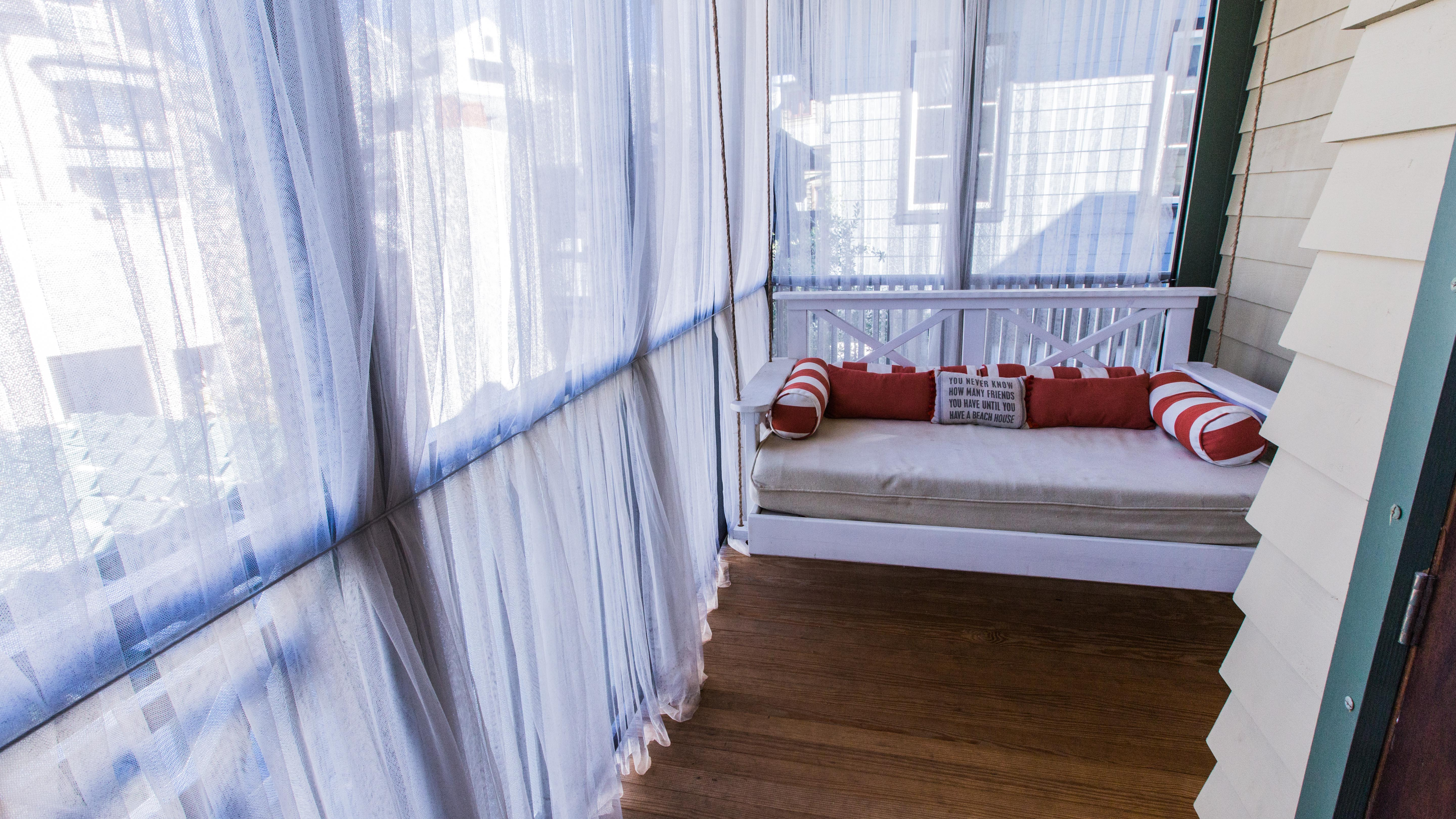 Screened porch features hanging swing bed and additional seating on opposite side