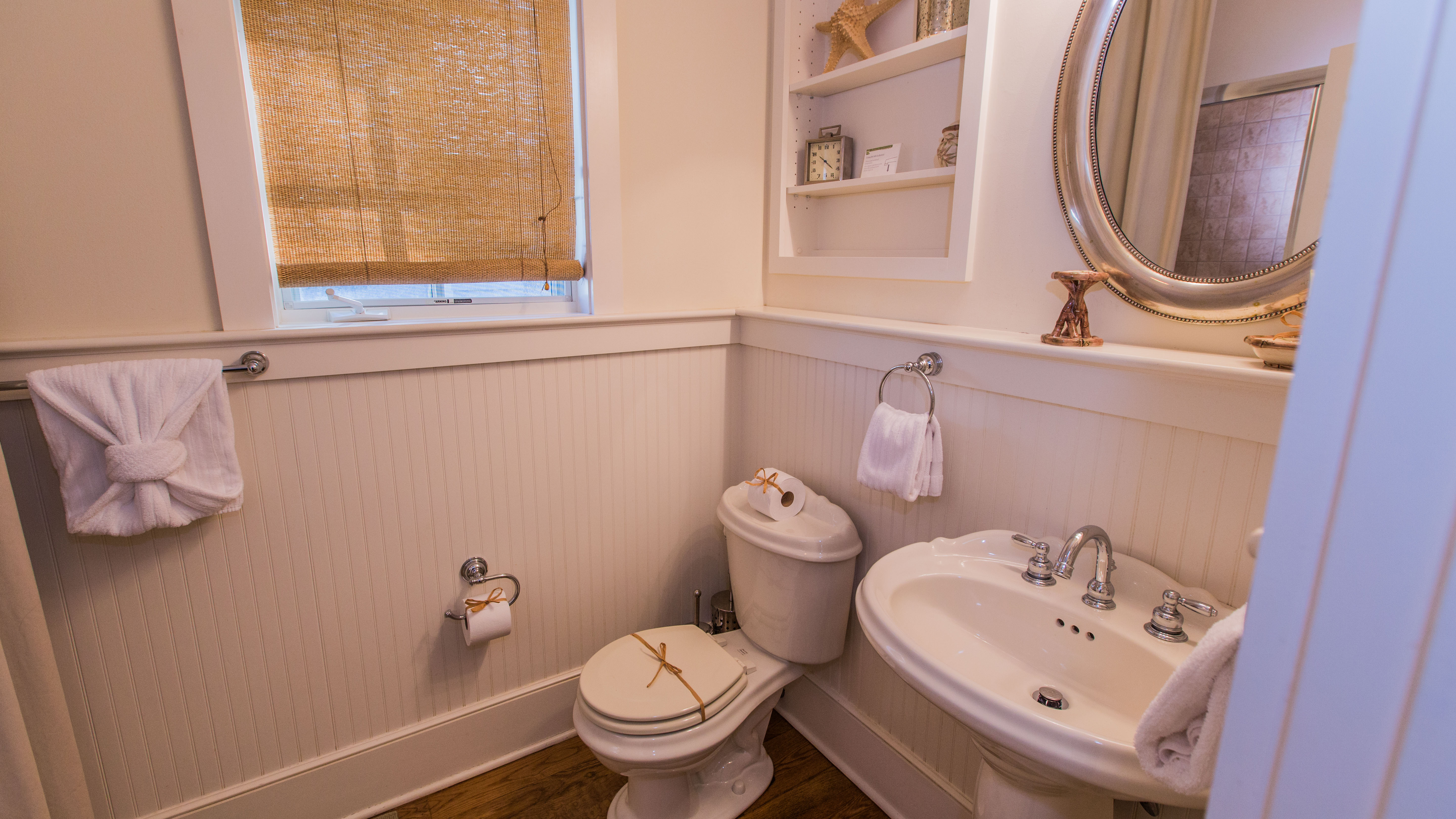 En suite bath features pedestal sink and tub/shower combination