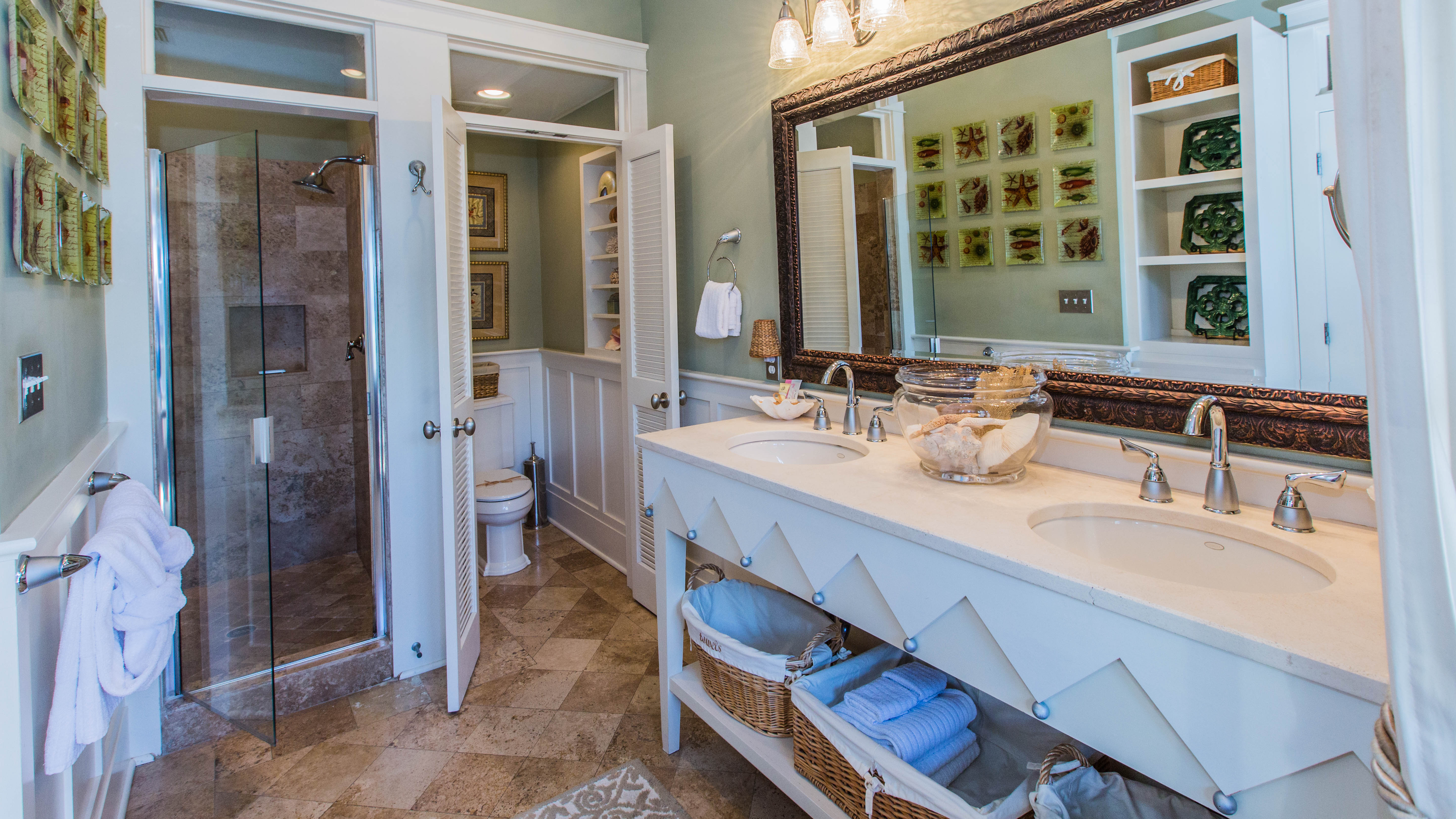 En suite bath features custom double sinks and travertine shower